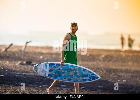 Indonesia, Bali, surfer di camminare sulla spiaggia Foto Stock