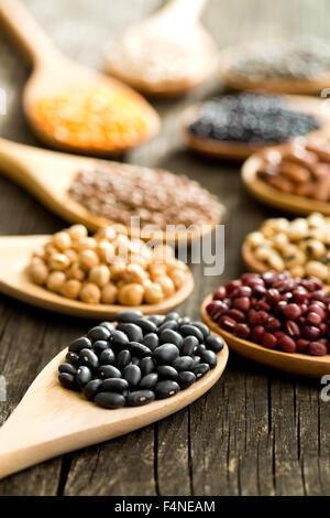Vari i legumi secchi in cucchiai di legno sul vecchio tavolo