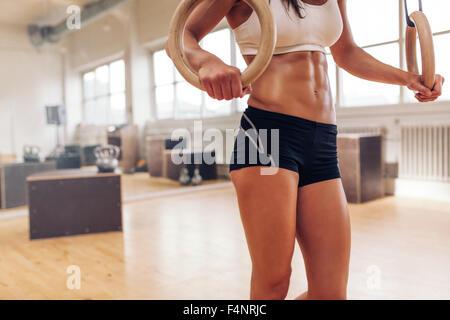 Tagliate il colpo di una donna di mani tenendo saldamente su di una coppia di anelli di ginnastica. Atleta femminile Foto Stock