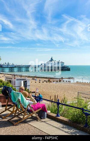 Due donne anziane seduta sul lungomare con la spiaggia e il molo dietro, Grand Parade, Eastbourne, East Sussex, Foto Stock