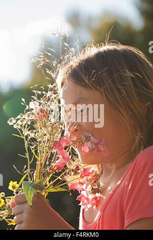 La ragazza (10-11) azienda mazzetto di fiori selvatici Foto Stock