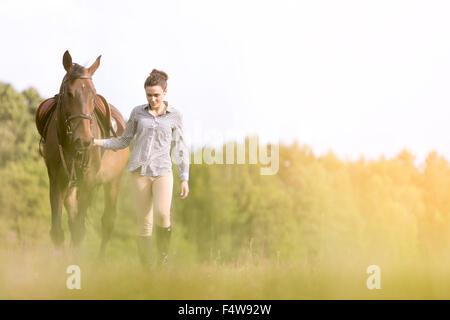 Donna passeggiate a cavallo in campo rurale Foto Stock