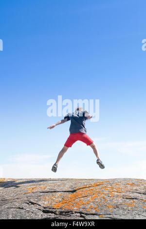 La Svezia, Uppland, Runmaro, Barrskar, ragazzo (6-7) il salto sulla roccia, vista posteriore Foto Stock