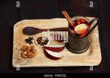 Hot Toddy (vin brulé, punch) con mele e rosa canina servita su legno rustico vassoio con mandorle scure su un tavolo Foto Stock