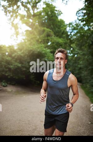 Montare atletico pareggiatore maschio in esecuzione attraverso un parco boscoso verso la telecamera con un aspetto Foto Stock