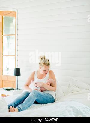 Metà donna adulta holding baby boy (0-1 mesi) nelle sue braccia Foto Stock