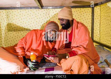 Due sadhus, uomini santi, stanno giocando con uno smartphone in una tenda Foto Stock