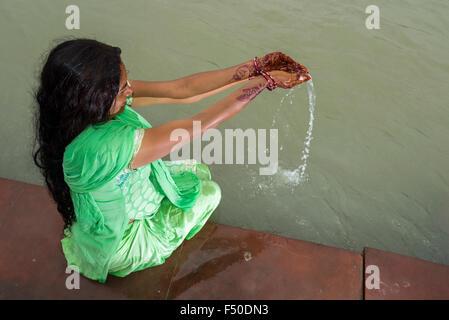 Una giovane donna con lunghi capelli neri, Henna dipinto di mani e un abito verde è pregare presso la ghats del Foto Stock