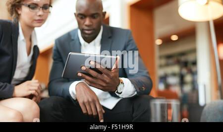 Colpo di imprenditori seduti insieme guardando digitale compressa. Focus sulla tavoletta digitale in mano d'uomo. Foto Stock