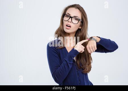 Ritratto di una giovane donna di puntare il dito su orologio da polso isolato su uno sfondo bianco Foto Stock