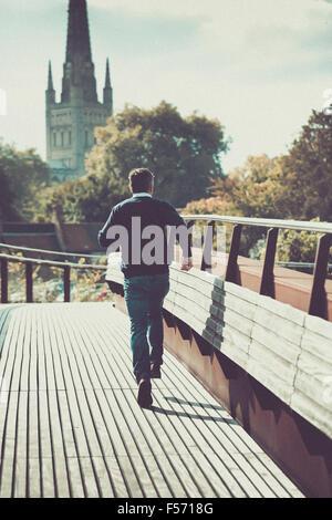 Uomo che corre attraverso il ponte urbano con la chiesa in background Foto Stock