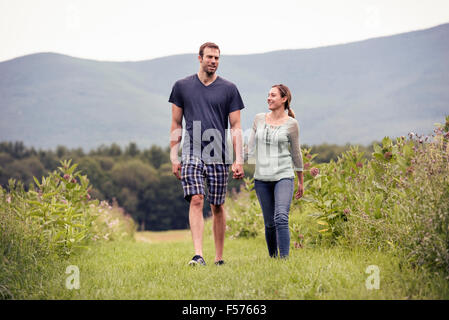 Un giovane uomo e donna a piedi attraverso un prato tenendo le mani. Foto Stock