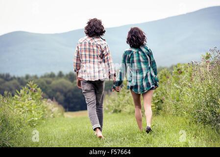 Un giovane uomo e donna a piedi attraverso un prato mano nella mano, in vista posteriore Foto Stock