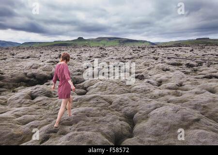 Moda Donna camminare a piedi scalzi nel campo di lava in Islanda Foto Stock