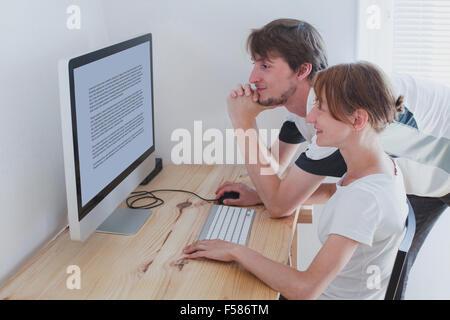 Coppia giovane guardare il computer a casa Foto Stock