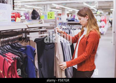 Donna scelta di vestiti in negozio Foto Stock