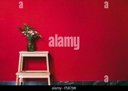 Semplice design di interni, fiori in vaso sulla parete rossa sullo sfondo Foto Stock