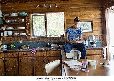 Uomo con tavoletta digitale in cucina di cabina Foto Stock