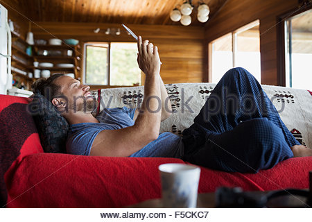 L'uomo posa sul divano di cabina con tavoletta digitale Foto Stock
