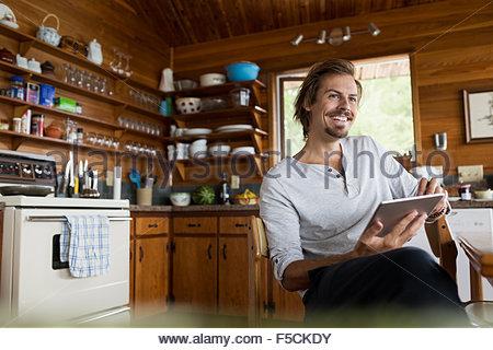 Uomo sorridente con tavoletta digitale cabin tavolo da cucina Foto Stock