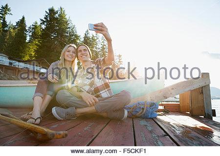 Sorridente coppia giovane tenendo selfie dock nei pressi di canoa Foto Stock