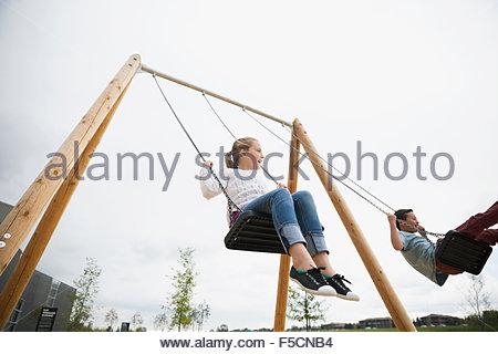 Un ragazzo e una ragazza swinging presso il parco giochi Foto Stock