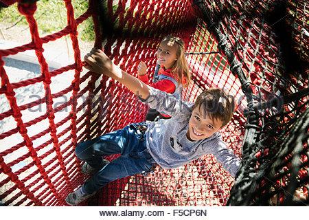 Ritratto sorridente un ragazzo e una ragazza arrampicata corda net Foto Stock