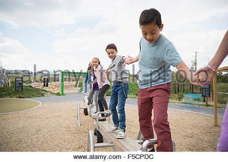 Kids bilanciamento sulla lunga altalena al parco giochi Foto Stock