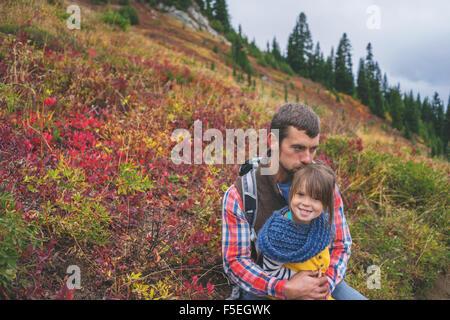 Padre seduto con sua figlia in montagna Foto Stock
