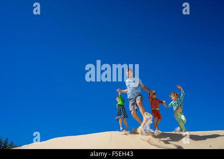 Padre e tre bambini correre giù per una duna di sabbia Foto Stock
