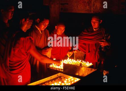 Monaci buddisti tibetani e nun accendendo candele di notte ( Nepal) Foto Stock