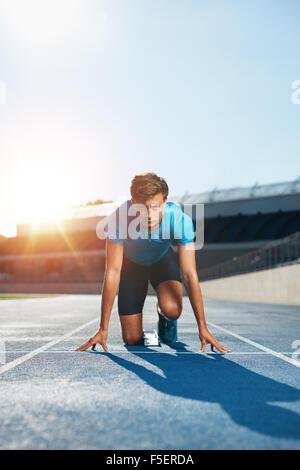 Colpo verticale del giovane maschio runner tenendo pronti per avviare la posizione di fronte alla telecamera. In Foto Stock