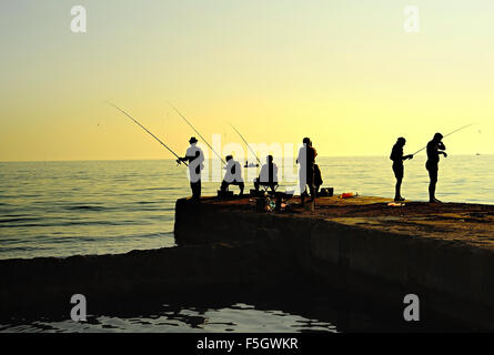 Gruppo di pescatori su un molo al tramonto. Penisola di Crimea Foto Stock