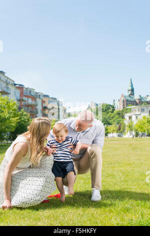 La Svezia Sodermanland, Nacka, Finnboda Hamn, genitori assistere figlio (18-23 mesi) con primi passi Foto Stock