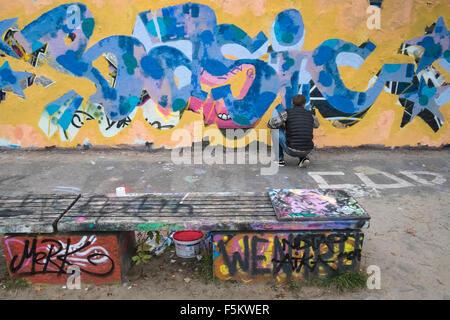 Graffiti artist verniciatura a spruzzo parte del vecchio Muro di Berlino, il Mauerpark, Prenzlauer Berg di Berlino, Foto Stock