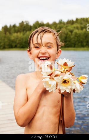 La Svezia, Uppland, Runmaro, Barrskar, ritratto del ragazzo (6-7) tenendo i fiori Foto Stock