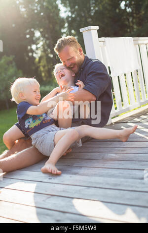 La Svezia, arcipelago di Stoccolma, Grasko, Padre giocare con figli (4-5, 6-7) per esterni Foto Stock