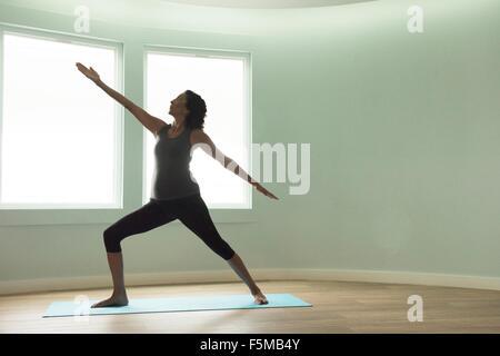 Donna matura fare yoga warrior pongono in camera ricurva