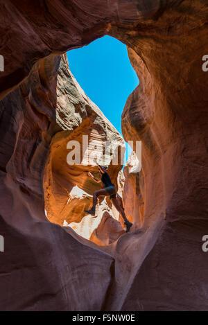 Ragazza escursionista Jumping all'interno dello Slot pieghevole Canyon dello Utah Foto Stock