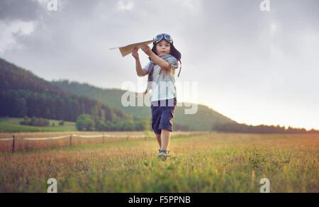 Carino piccolo ragazzo giocando il piano della carta Foto Stock