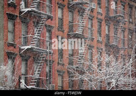 Facciata del Chelsea in mattoni con fuoco sfugge coperto di neve durante una nevicata invernale, Manhattan New York City