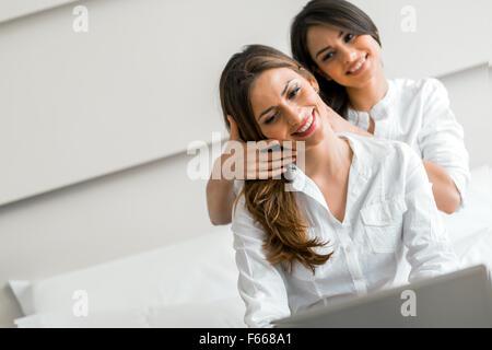 Gorgeous brunettes alla moda in camicie lavorando su un computer portatile mentre nel letto Foto Stock