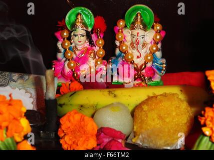 Dea devozionale Maa Lakshmi e signore Ganesha statua con alcuni dolci e frutta Foto Stock