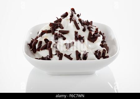 Yogurt gelato guarnito con i riccioli di cioccolato Foto Stock