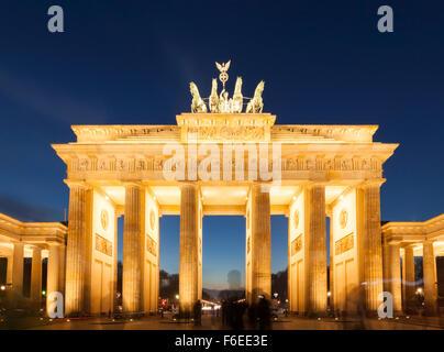 Berlino, illuminato dalla Porta di Brandeburgo al tramonto, una lunga esposizione shot con sagome fantasma di turisti nella parte anteriore Foto Stock