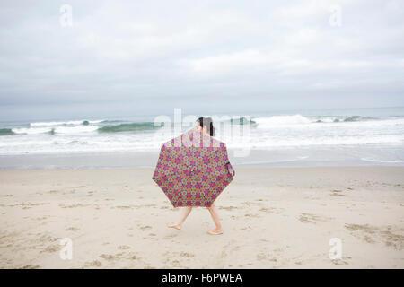 Donna che cammina con ombrellone in spiaggia Foto Stock