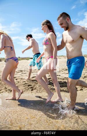 Gruppo di amici a piedi lungo la spiaggia Foto Stock