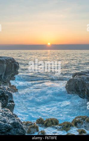 Alba sulle formazioni rocciose sulla spiaggia Foto Stock