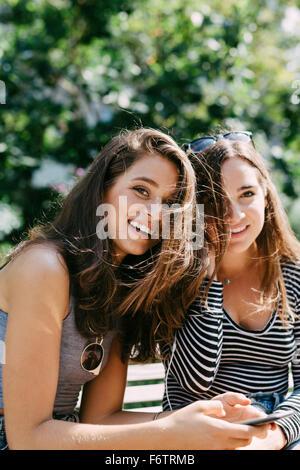 Due amici felici ascoltando la musica con gli auricolari Foto Stock