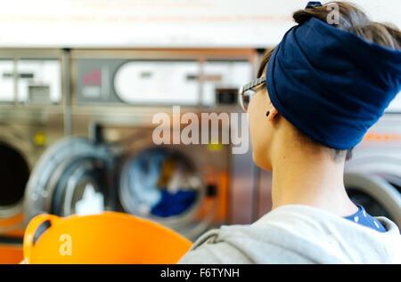 Vista posteriore della giovane donna in una lavanderia a gettoni Foto Stock